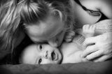 Mother kissing her smiling baby